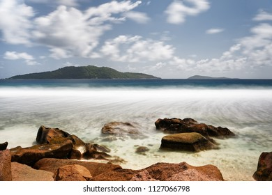 Surf on a beach with stones, water movement in long exposure, islands in the background, sky with clouds - Location: Seychelles, La Digue