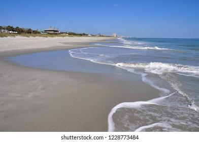Surf and sand along a empty beach.