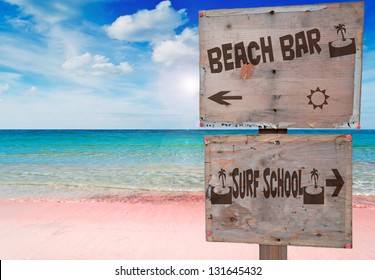 surf school and beach bar sign in a beautiful pink beach under a dramatic sky with sun reflection