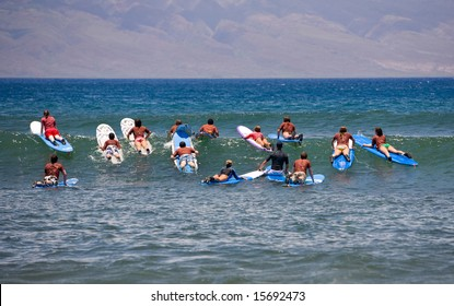 Surf school - several surfboarding students headed into an ocean swell