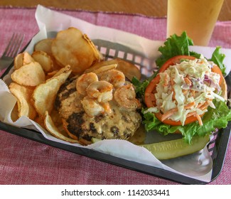 Surf and Turf Burger with shrimp and cheese.  Basket of food with a side of chips and a cold beer