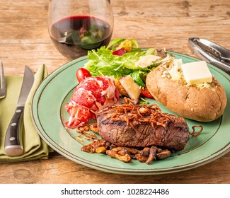Surf and Turf dinner with grilled beef tenderloin and lobster tail.  A green salad and baked potato are plated.  A glass of wine finishes.  Fried shallots and mushrooms garnish the beef.