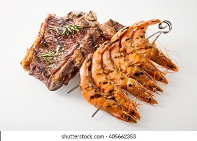 Surf and turf marinated spicy T-bone beef steak and skewered queen prawns seasoned with rosemary, high angle view on white