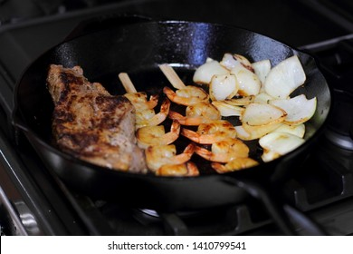 Surf and turf with NY strip and shrimp kabobs with grilled onions, in a cast iron skillet.
