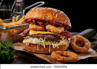 Surf and turf seafood and meat burger with fried squid rings, melted cheese, crispy bacon and a beef patty served on a wooden board with side potato chips