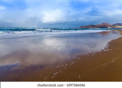 Surf waves at the coast of the Atlantic Ocean. The sky is reflected in water