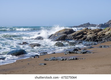 Surf and waves on a rocky coast with grey overcast skies