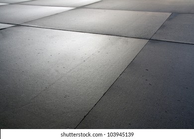 surface of asphalt or concrete few hours after some rain, with reflecting soft light coming from the cloudy sky