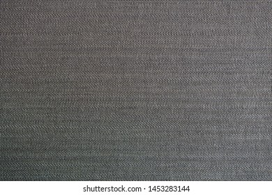 A surface of a beautiful grey woven canvas. Lovely neutral colored background made of fabric. Photographed with a macro lens.
