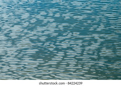 Surface of a blue lake rippled by a light breeze