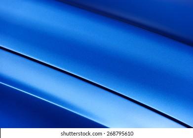 Surface of blue sport sedan car metal hood; part of vehicle bodywork