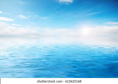 The surface of a calm sea with a small ripple under a sunny cloudy sky
