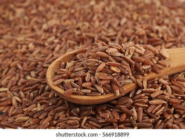 Surface coated with the brown rice grains and wooden serving spoon over it, as a food and cooking backdrop composition with a shallow depth of field