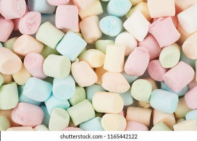 Surface coated with colorful mini marshmallows as a backdrop close-up texture composition