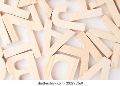 Surface covered with multiple wooden letters as a background composition