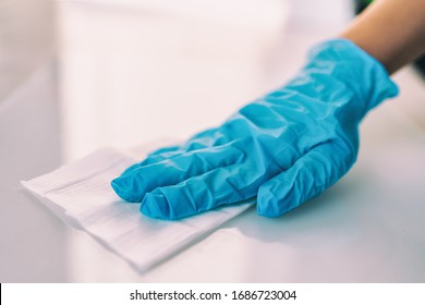 Surface disinfecting home cleaning with sanitizing antibacterial wipes protection against COVID-19 spreading wearing medical blue gloves. Sanitize surfaces prevention in hospitals and public spaces. - Shutterstock ID 1686723004