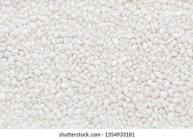 Surface of fine, natural white pearls. Festive, wedding background, texture. Flat lay, top view, copy space