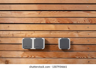 Surface of a freshly painted planking of a facade of wooden slats in the color mahogany and three 220 volt sockets