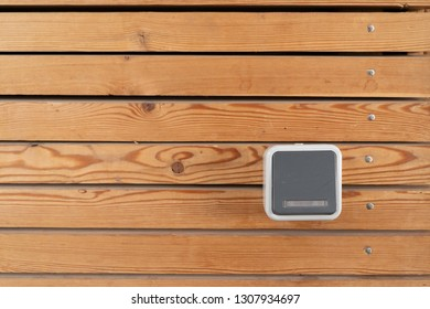 Surface of a freshly painted planking of a facade of horizontal wooden slats in the color mahogany and one 220 volt sockets