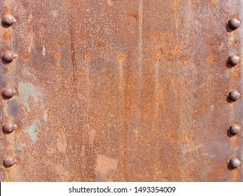 surface is full of rust of steel pole or metal beam with row of rivet heads, structure of large buildings weathered and rusty, abstract heavy industrial texture background, close up with copy space