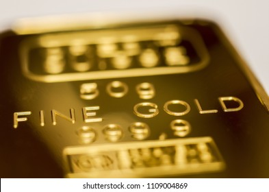 The surface of gold bullion. The texture of the surface of the minted gold bar. Selective focus, shallow DOF.
