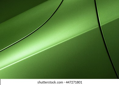 Surface of green sport sedan car, detail of metal hood, fender and door of vehicle bodywork