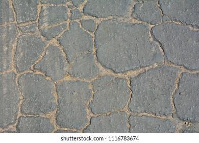 Surface of grey cracked asphalt background.