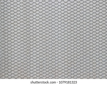 Surface of a latticed metal fence with diamond-shaped elements in front of a wall made of narrow plastic strips