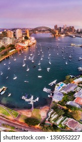 Surface of Lavender bay on Sydney harbour covered by floating yachts around jetties, wharfs and marina in view of the Sydney harbour bridge and major city landmarks in vertical sunset panorama.