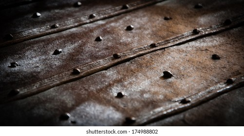 Surface of the old rusty bound chest with rivets and nail heads. Light and shadow game. Vintage background.