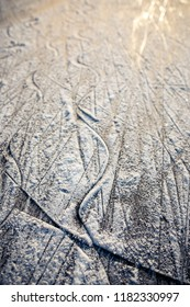 Surface of outdoor ice with snow at sunset, replete with skate marks. Abstract Ice background