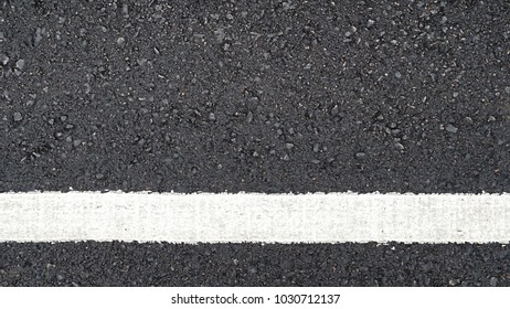 Surface rough and wet of asphalt after the rain, Grey with white line on the road and small rock, Texture Background, Top view