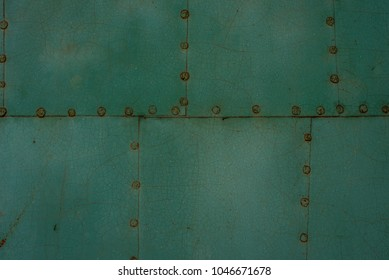 Surface from sheets of metal painted in green color fastened with nails