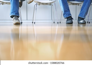 Surface shot of men sitting in chairs in waiting room
