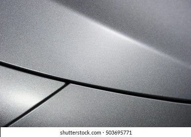 Surface of silver sport sedan car, detail of metal hood and fender of vehicle bodywork
