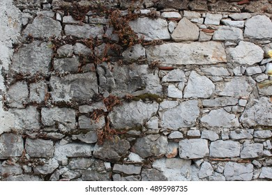 the surface texture of the old wall built of stones with a small amount of the solution
