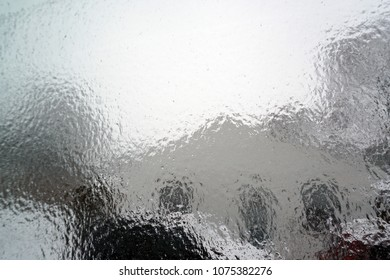 Surface of window after winter storm covered with rain, sleet, and ice