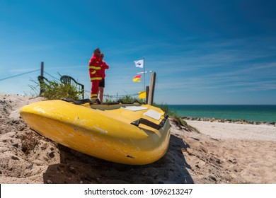 Surfboard of lifeguard kept on sand at Hiddensee beach, Baltic Sea, DLRG, Germany