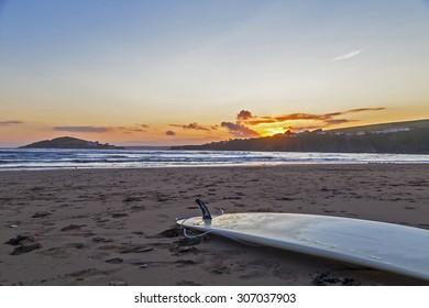 Surfboard lying on a south devon beach UK