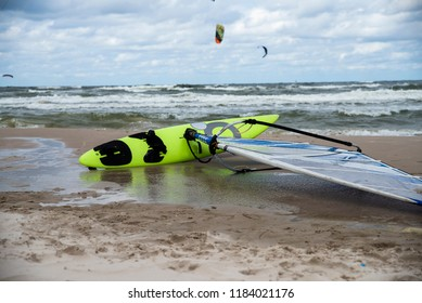 surfboard on the beach, kitesurfing in the background