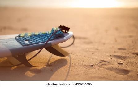 Surfboard on the beach at sunse