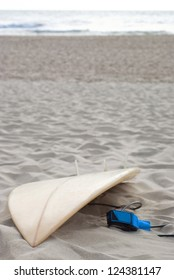 Surfboard on remote beach  with ocean in background