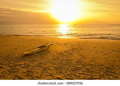 Surfboard on the sand beach in sunset at phuket Thailand