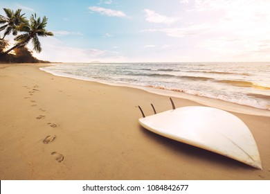 Surfboard on tropical beach at sunrise in summer. seascape of summer beach with sea, blue sky background.