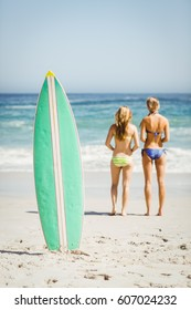 Surfboard in sand and rear view of two women looking at sea on a sunny day