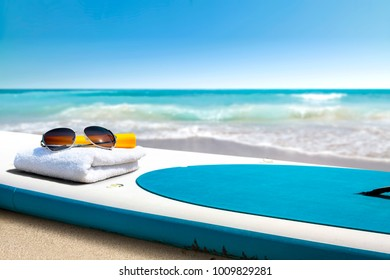 Surfboard and summer time on beach. Free space for your decoration.