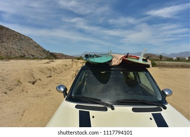 surfboards on roof of car at beach in Baja, Mexico
