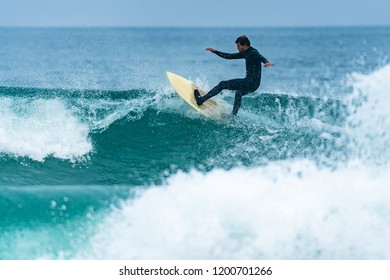 Surfer in action on the ocean waves on a cloudy day.