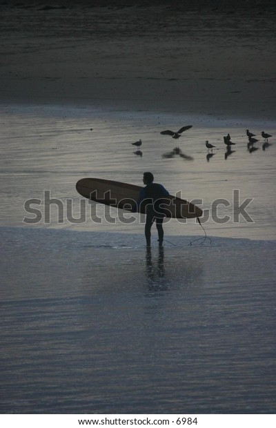surfer approaching the ocean with board under arm