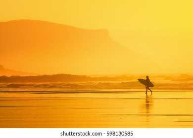 surfer in the beach at the sunset